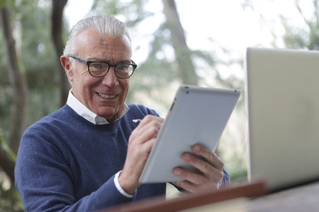 man-in-blue-sweater-holding-white-tablet-computer-3783249